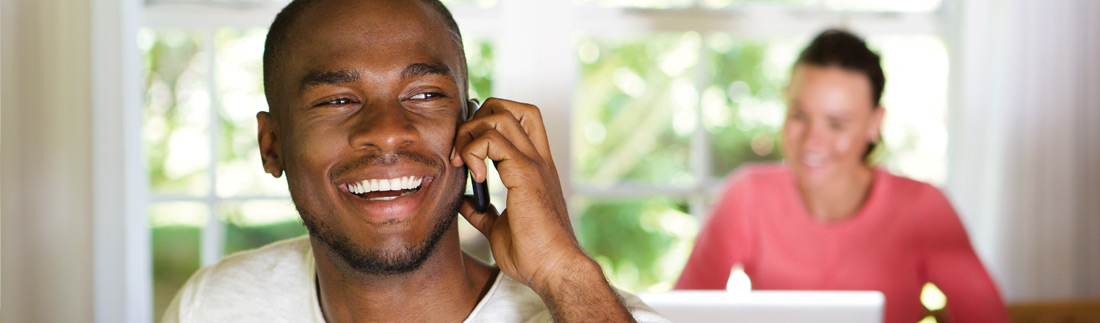 Young, happy black male on the phone.
